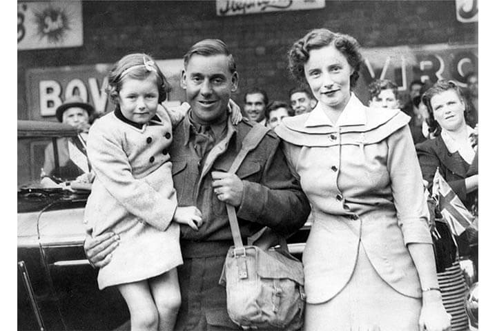 Having just returned from three years in a Japanese prisoner of war camp, a man stands with his wife and daughter.