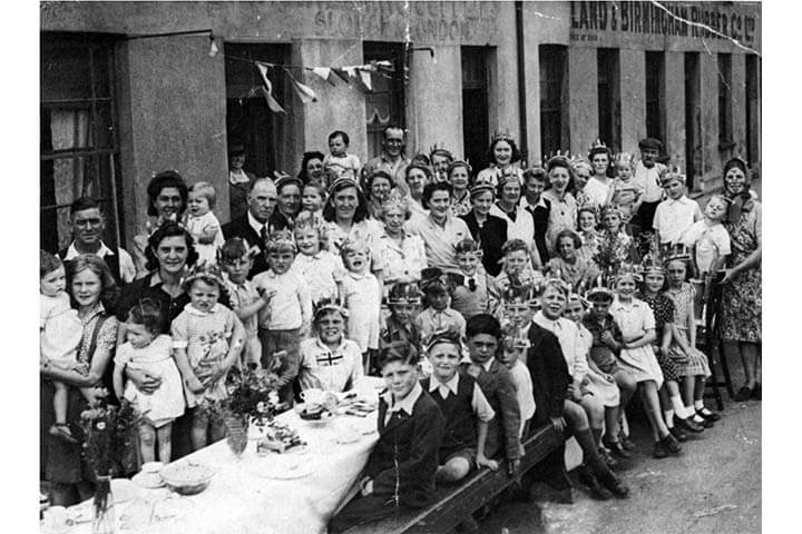 Black and white photo. People around large table in the street pose for photograph.