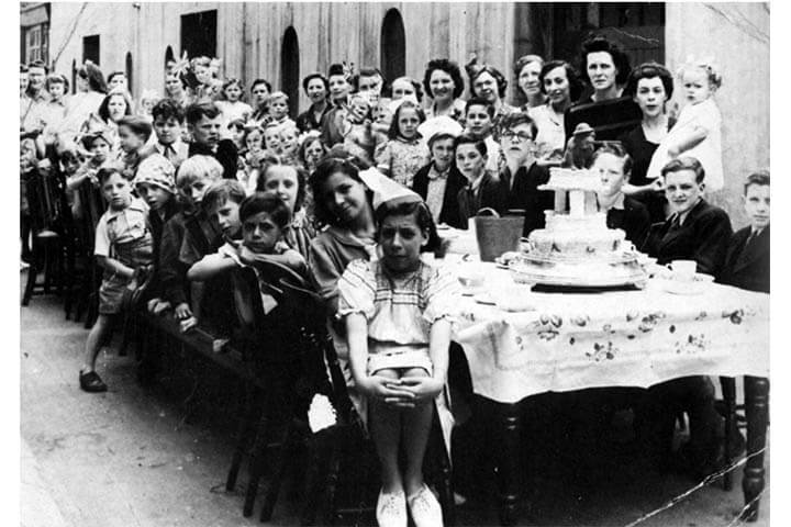 Black and white photo. People around large table, in the street, pose for photograph. A tiered cake is on the table.