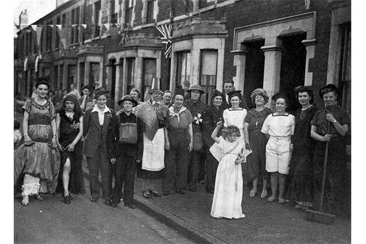 Black and white photo. People on street wearing fancy dress, pose for photo.